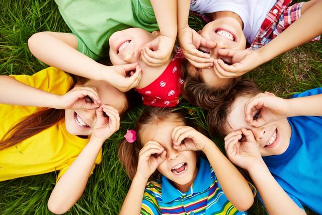 grupa dzieci bawiąca sięna trawie