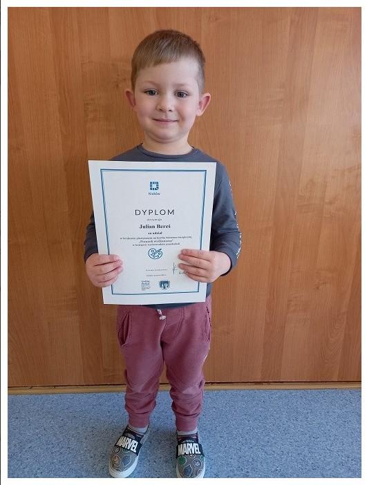 chłopczyk trzymajacy dyplom