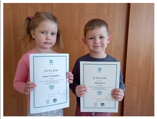 dzieci trzymajace dyplomy