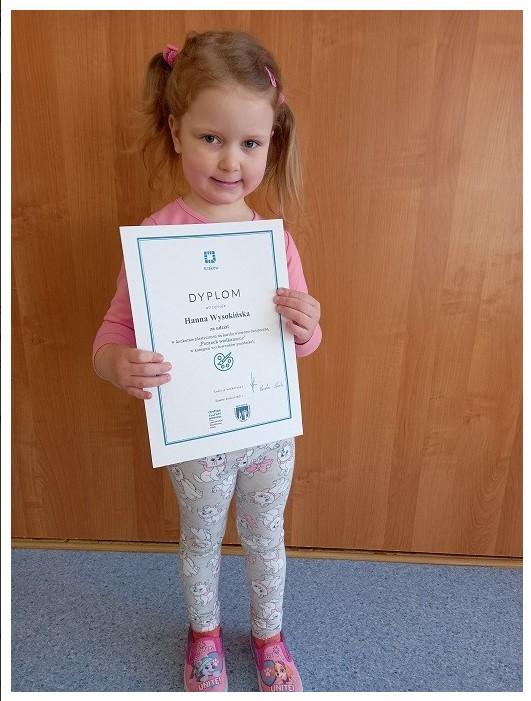 dziewczynka trzymajaca dyplom