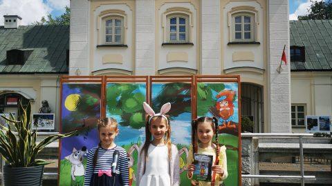 trzy dziewczynki na scenie. Ostatnia z nich trzyma broszurę z zajaczkiem