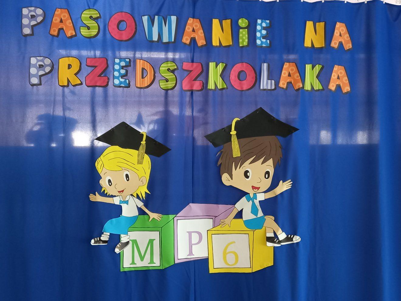 dekoracja pasowanie na przedszkolaka. Obrazek dzieci - dziewczynka i chłopiec siedzi na klockach z logo MP6