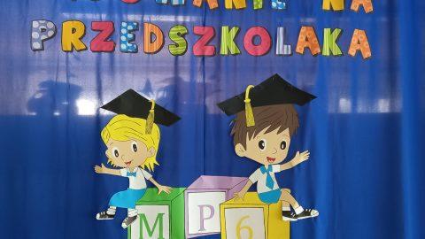 napis pasowanie na przedszkolaka. obrazek dziewczynki i chłopca siedzących na klockach z logo MP6