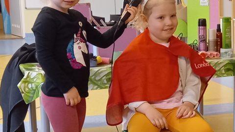 dwie dziewczynki w przedszkolnym salonie fryzjerskim