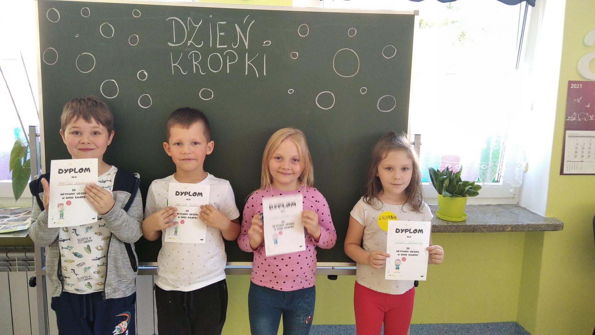 dwóch chłopców i dwie dziewczynki z dyplomami
